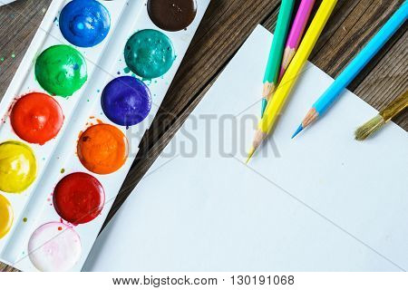 Art tools. Watercolor Paints and brushes with blank white paper  on wooden background close up.