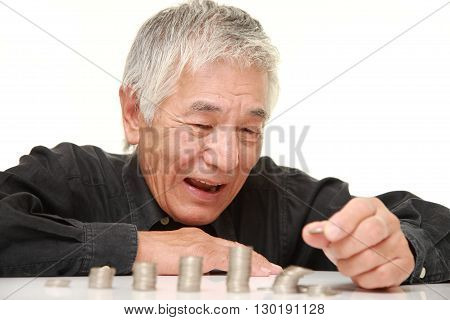 stack of coins collapsed when man adds a coin