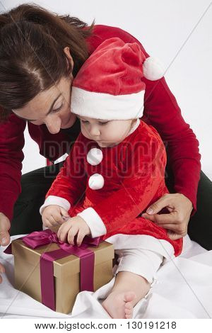 one year age caucasian blonde baby Santa Claus disguise with brunette woman mother red cardigan green trousers opening golden box gift Christmas on white background