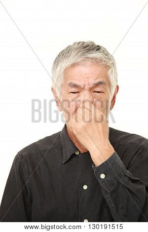 portrait of senior Japanese man holding his nose because of a bad smell on white background