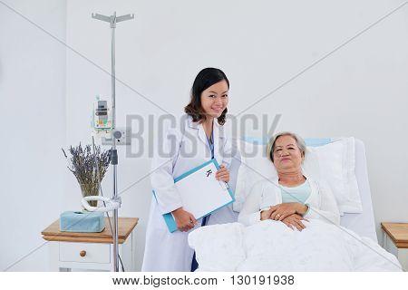 Portrait of nurse and senior female patient in bed