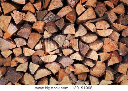 Background of chopped firewood stacked up on top of each other in a pile. Pile of chopped fire wood prepared for winter. Old firewood pile background