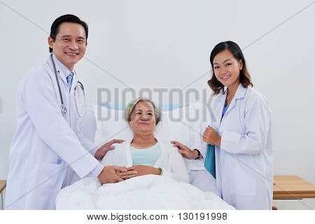 Cheerful senior woman with doctor and nurse standing on each side of her bed
