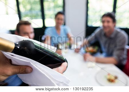 Close-up of waiter carrying a wine bottle in a restaurant