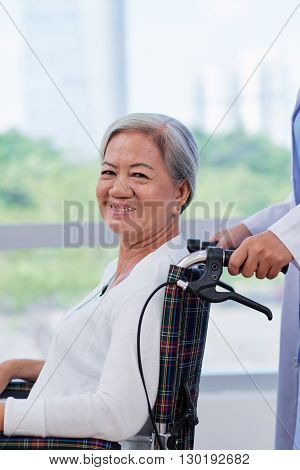 Cheerful aged woman in wheelchair after treatment in hospital