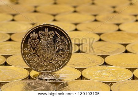 British money pound coin showing heraldic lion unicorn shield and crown on a background of pound coins.