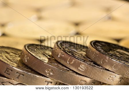 British money pound coins spread out in a fallen stack.