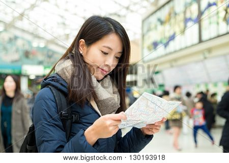 Woman look at map in train station