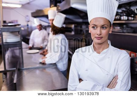 Chef standing in commercial kitchen and three chefs discussing In background