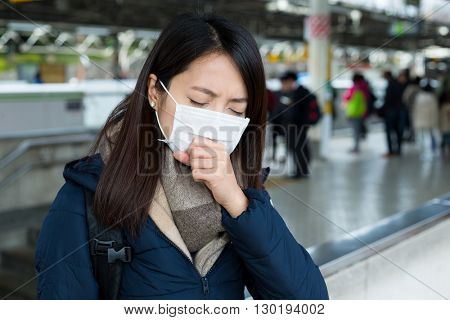Woman feeling unwell and wearing face mask in train station