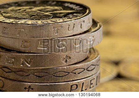 Close up of British money pound coins stacked up.