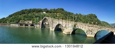 Panoramic view of a unique stone bridge. The medieval Ponte Maddalena or Devils Bridge in Tuscany. Unrecognizable people at the crest of the bridge are included for scale.