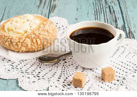 A cup of coffee and cheesecake with cottage cheese on a openwork napkin on a blue wooden background.