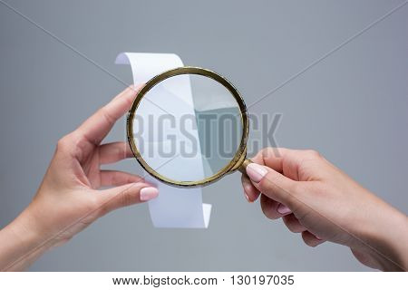 The female hands with  empty transaction paper or paper check on gray background and magnifier