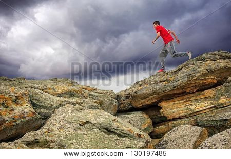 Sportsman running jumping over rocks in mountain area. Training running and jumping in difficult conditions in a beautiful nature with stormy dramatic sky
