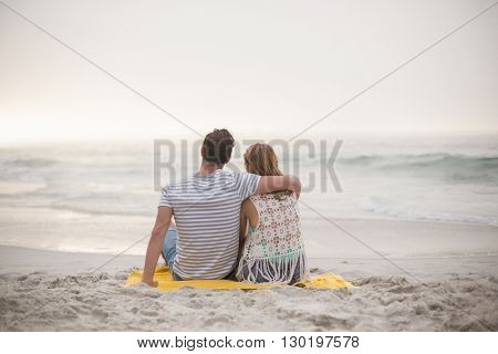 Rear view of couple sitting together on the beach