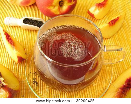 Black tea with peach and nectarine in cup