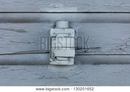 Old electric outlet box with cracking and peeling lead paint off of wood sliding.