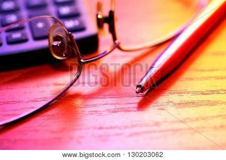 Colorful still life with pen near spectacles and calculator