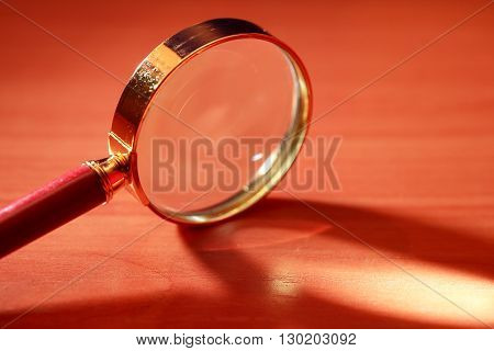 Magnifying glass with long shadow on wooden table