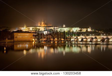 Charles bridge and St. Vitus cathedral view during rainy night Prague Czech republic