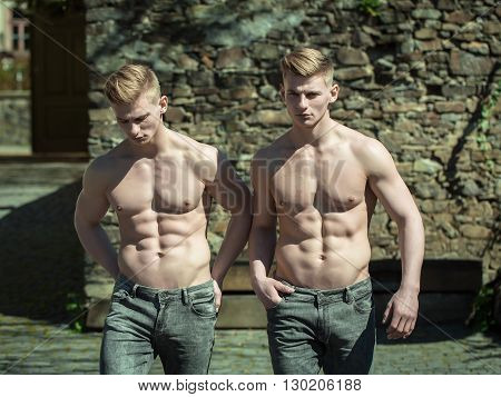 Twin muscular bare-chested young men brothers sexy models walk shirtless in jeans on courtyard background