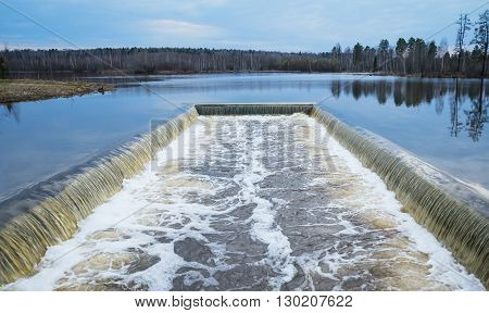Hydraulic structure in front of the dam on forest lake in spring evening.