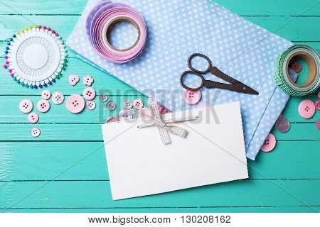 Sewing thread - buttons scissors fabric and empty tag on turquoise wooden background. Selective focus. Scrapbboking. Flat lay. Place for text.