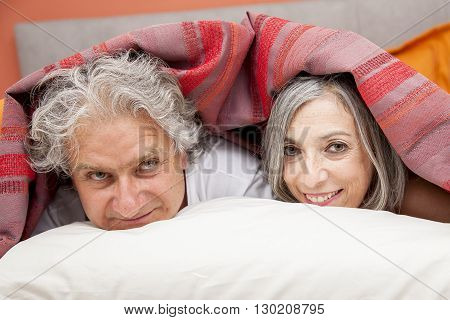 Close-up Of A Mature Couple Relaxing In Bed At Home