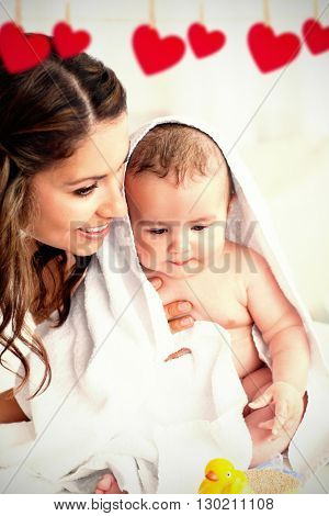 Hearts hanging on a line against delighted mother drying her baby after his bath