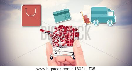 Digital shopping diagram on a white background against composite image of hand showing house