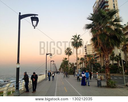 The famous seaside Corniche on sunset, Beirut, Lebanon. Beirut, Lebanon -  December 24, 2015: People take their sunset walk on the famous Corniche (seaside promenade) in Beirut, Lebanon