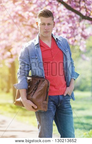 young man standing next to cherry blossom holding a bag