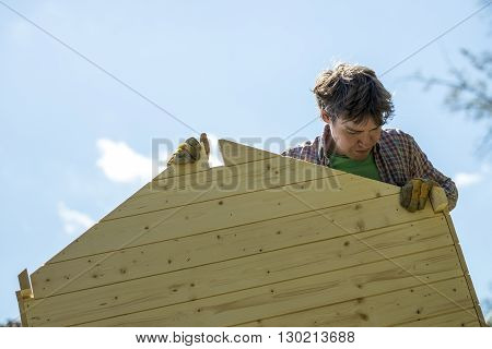Low angle view of a young man assembling a wooden playhouse in a DIY concept.