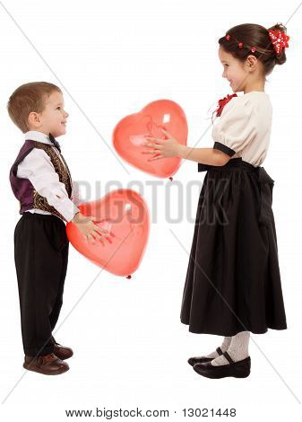Little children give each other red balloons