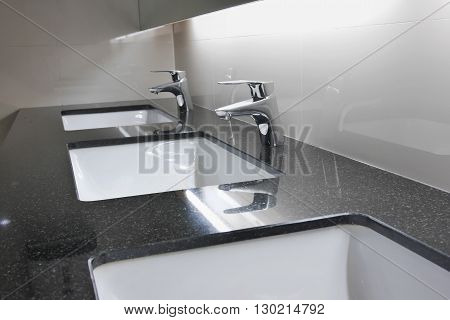 White Washbasins And Faucet On Granite Counter In Restroom