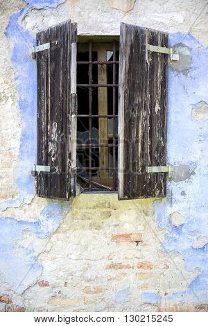 Old windows of an abandoned farmhouse .