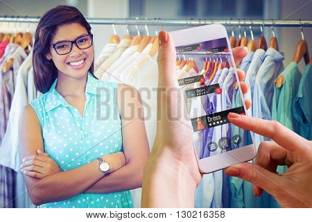 Hand holding smartphone against happy shopper smiling at camera