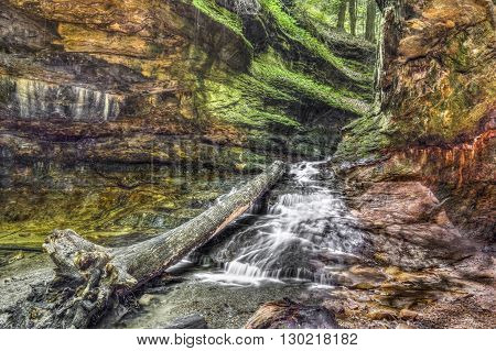 Water cascades over colorful sandstone from a narrow passage with green rocky walls In Indiana's Turkey Run State Park.