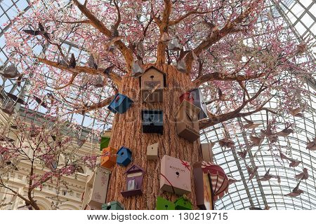 MOSCOW - APRIL 13: Artificial tree birds and birdhouses at GUM store on April 13 2016 in Moscow. GUM is the large store in the Kitai-gorod part of Moscow facing Red Square.