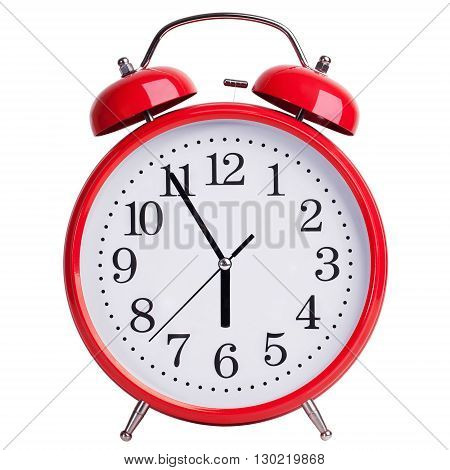 Red round alarm clock shows five minutes to six