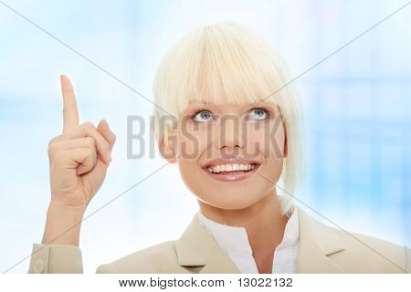 Young pretty office woman specifies with finger to up Over abstract blue background