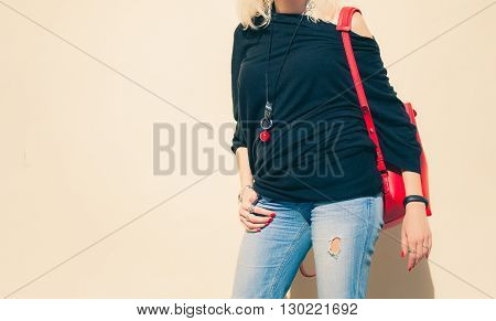 Fashionable beautiful big red backpack on the arm of the girl in a fashionable jeans, posing near the wall on a warm summer night. Warm color