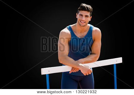 Portrait of sportsman is smiling and posing on a hurdle