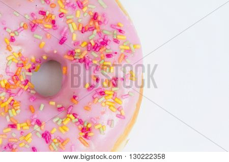 A large donut with pink icing and sprinkles on an isolated white background,