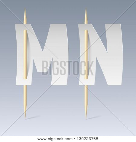 White paper cut font on toothpicks on grey background. M and N letters