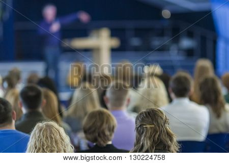 Conferences Concept and Ideas. Male Lecturer Explaining On Stage In front of the Large Group of People. Horizontal Image Composition
