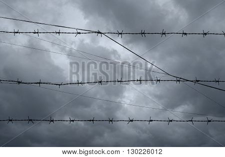 Silhouette of barbed wire over dark storm clouds before rain