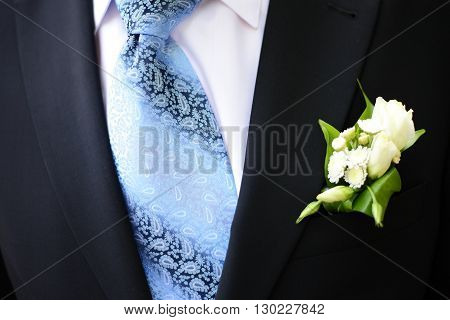 Groom ceremonial suit, boutonniere and blue tie
