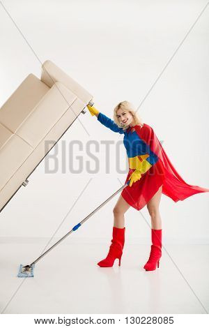 Superwoman lifting sofa when wiping floor under it